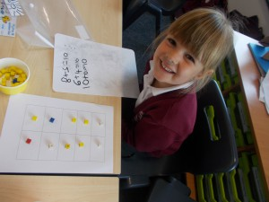 Lily using a 10 frame as a tool to work out all the different number bonds to 10.